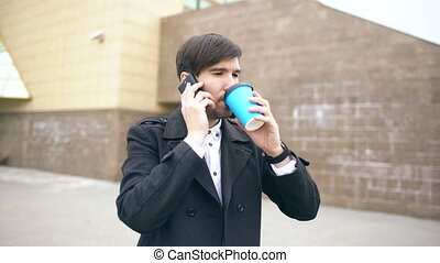 Dolly shot of young smiling businessman talking at smartphone and feels happy about making deal walks near office buildings