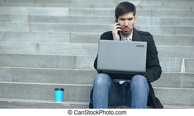 Young business man with laptop computer having stress after phone call and sitting on stairs in street. Businessman having deal problems at work concept