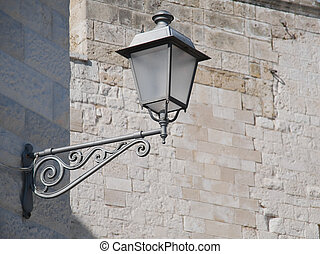 Closeup of old style street-lamp on a wall.