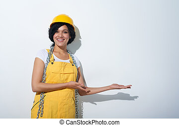 Happy woman builder wearing yellow protect helmet showing blank copy space