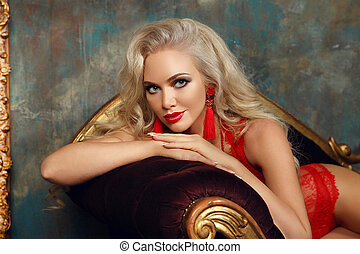 Beautiful fashion smiling woman with red lips makeup and wavy hair style, french manicured nails. Glamour lady posing on sofa in luxury interior.