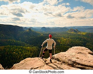 Hiker in grey t-shirt, medicine crutch and leg fixed in...