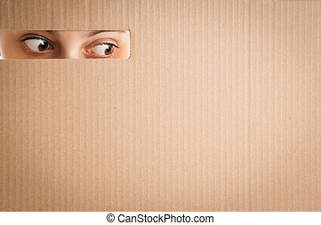 woman looking through the hole in cardboard - surprised...