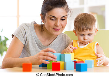 Young mummy and her kid play with cubes toys in nursery