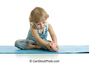 Child practicing yoga, stretching in exercise wearing...