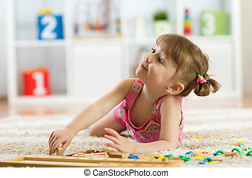 Cute little girl playing with educational toy blocks in a sunny kindergarten room. Kids playing. Children at day care.