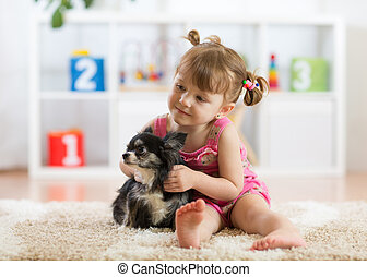 kd and dog play in a nursery