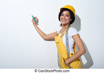 Happy woman builder wearing yellow protect helmet going to...
