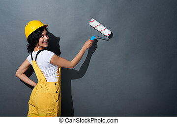 Happy smiling woman builder wearing yellow protect helmet -...