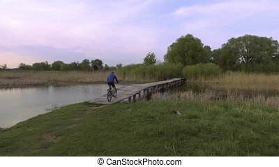man cyclist Rides on a wooden bridge across the river -...
