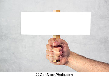 Male hand holding blank mockup banner sign as copy space -...