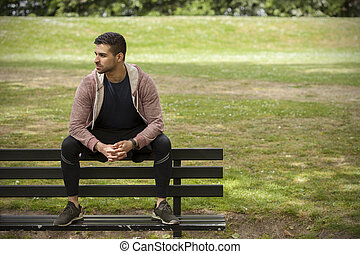 Fit Young Man Sitting on Bench in Park