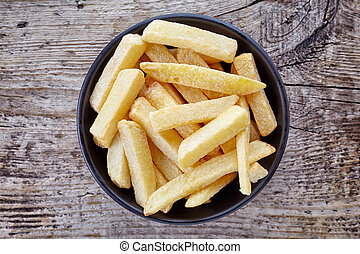 Bowl of french fries on wood, from above