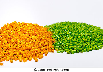 Green and orange plastic pellets on a white background....
