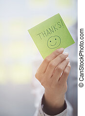 Thanks text on adhesive note - Woman holding sticky note...