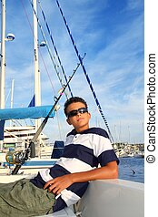 boy relaxed teenager on boat marina summer vacation