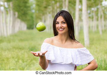 Cute girl with floating green apple in field.
