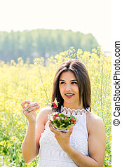 Vertical shot of girl eating salad in flower field.