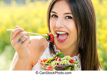 Fun portrait of cute girl eating green salad outdoors.