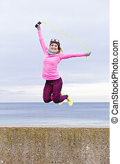 Woman training outdoor with jump rope on cold day