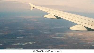 Airplane wing window seat view at lakes on earth, horizon...