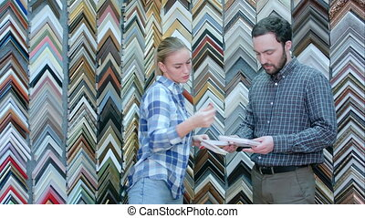 Female worker talking with customer about picture frame...