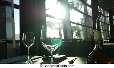 Glare of sun in an empty glass. Glasses on a table at a...