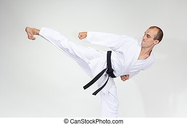 Adult athlete trains a kick on a gray background