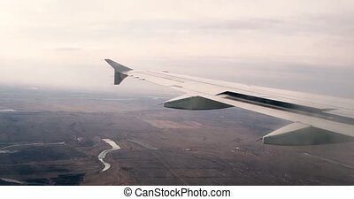 Wing of an airplane flying near above the earth. The view from an airplane window. Vintage grading. Wing part from airplane window.