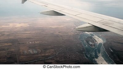 Wing from airplane window. Wing of an airliner flying above the earth with lakes. The view from an airplane window. Vintage grading