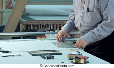 Male senior worker measure width and height of glass in...