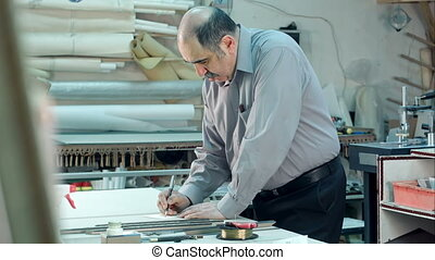 Senior male worker in workshope behind the counter writting...