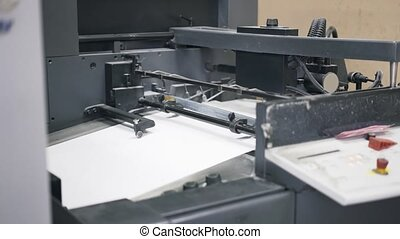 Pan shot of industrial printer making newspapers