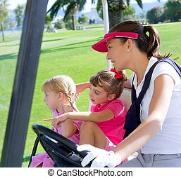 golf course family mother and daughters in buggy green grass...