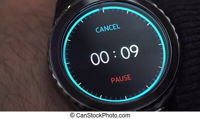 Closeup of a smart watch on male hand. The man turns on the timer. A countdown of 10 seconds before the end of time