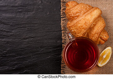 croissant with a cup of tea on a black stone background with copy space for your text. Top view