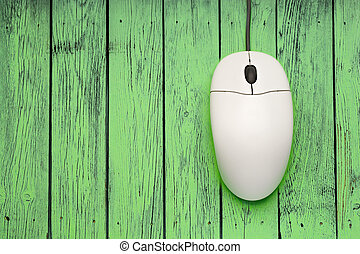 Computer mouse on green wooden background closeup