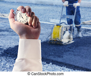 Worker use vibratory plate compactor and stopwatch in male...