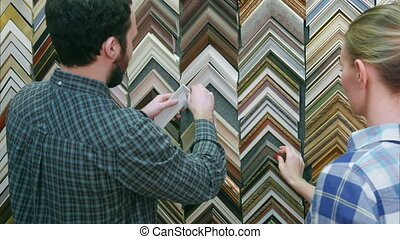 Young couple customer looking for frame for picture in...