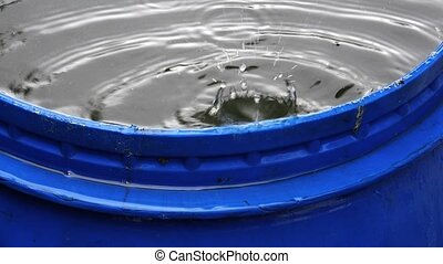 Barrel with water. Raindrops. 4K.