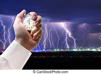 Night thunder lightning and stopwatch in male hand - Night...
