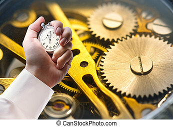 Clock inside mechanism and stopwatch in male hand -...