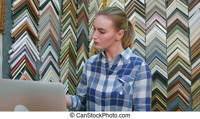 Portrait of a young female business owner behind the counter using laptop computer in her shop