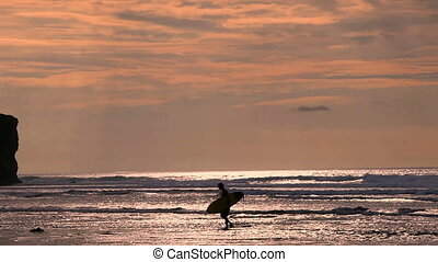 Surfer in silhouette walking with long surf boards at sunset...