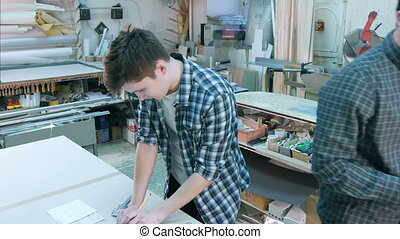 Portrait of a young male worker behind the desk construct frame in workshop