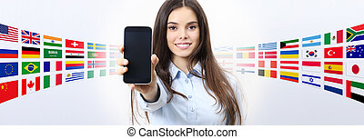 cheerful smiling woman showing blank smartphone screen, with international flags in background