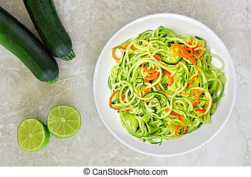 Healthy zucchini noodle dish with carrots and lime on white...