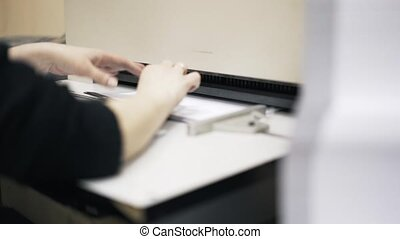 Woman worker inserting sheets of paper into machine - Woman...