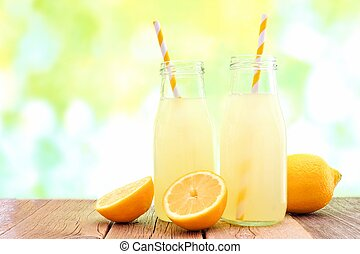 Two bottles of cold lemonade with lemon slices and straws...