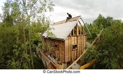 Workers dismantle and demolish the old wooden house. 4K. -...